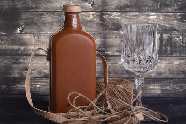 Garrafa de uísque e copo de vinho vazio em uma madeira preta