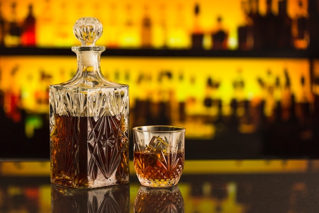Garrafa de uísque e copo no balcão de bar