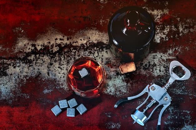 Garrafa de uísque maturado com saca-rolhas e um copo de licor com cubo de gelo preto reutilizável em uma mesa de madeira rústica com vista de cima para baixo