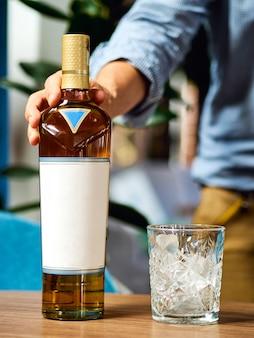 Garrafa de uísque na mão no copo de mesa com gelo