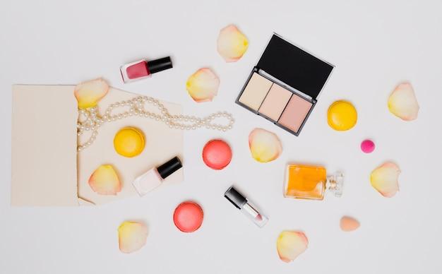 Garrafa de verniz para unhas; pétalas de rosa; colar; batom; macaroons e frasco de perfume isolado no fundo branco