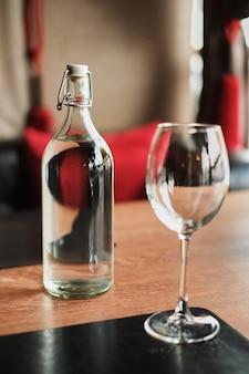 Garrafa de vidro alta de água e um copo vazio em uma mesa de madeira no caffe