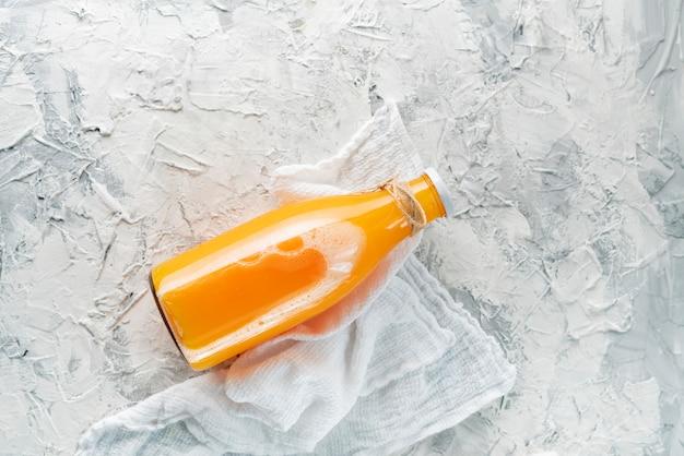 Garrafa de vidro com um suco de laranja espremido, cortado em torno de meio laranjas