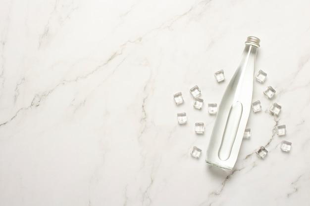 Garrafa de vidro de água e cubos de gelo em uma mesa de mármore.