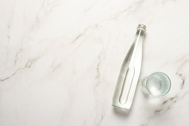 Garrafa de vidro de água e um copo de água em uma mesa de mármore.