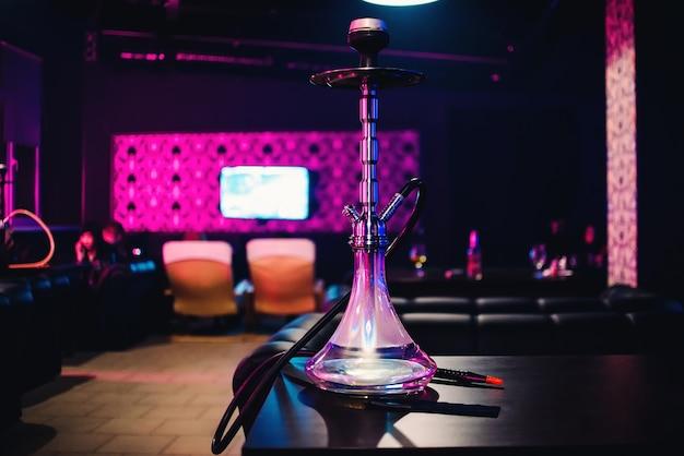 Garrafa de vidro de cachimbo de água para fumar tabaco em cafés na mesa