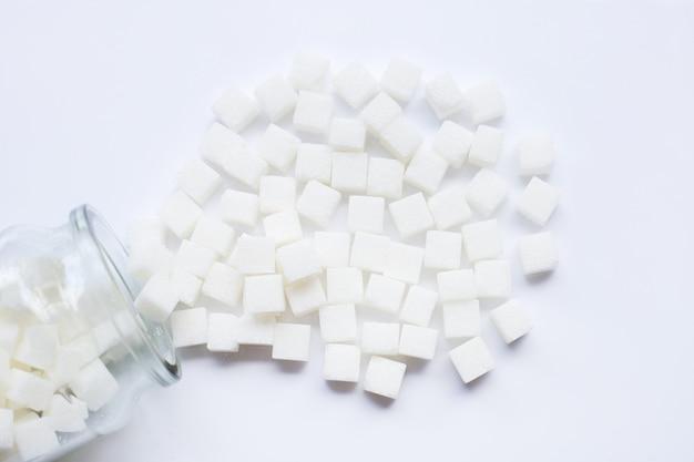Garrafa de vidro de cubos de açúcar no fundo branco.