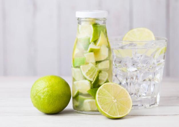 Garrafa de vidro de fatias de limão ainda água de frutas e limão cru em branco de madeira com cubos de vidro e gelo