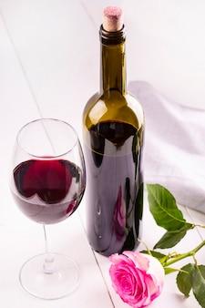 Garrafa de vidro de vinho com rolhas e rosa na mesa de madeira branca