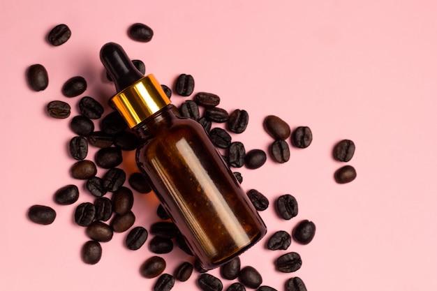 Garrafa de vidro marrom de óleo de café de vista superior e grãos de café bagunça rosa fundo pastel