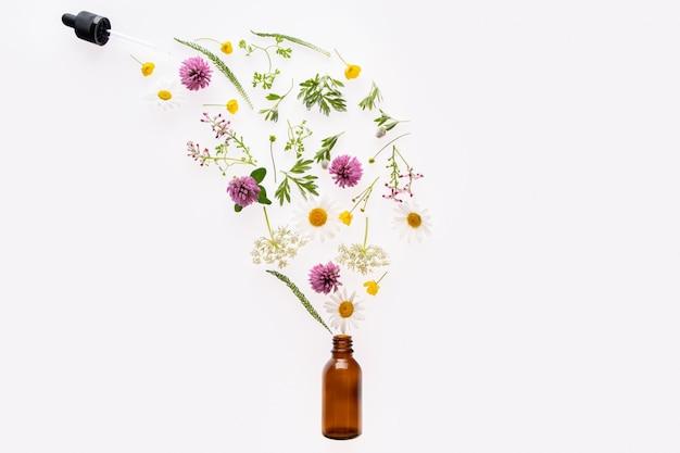 Garrafa de vidro marrom e flores silvestres e ervas derramam do conta-gotas.