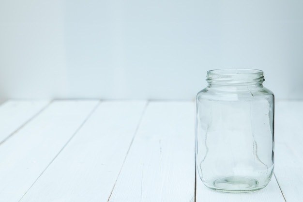 Garrafa de vidro vazia na tabela branca de madeira.