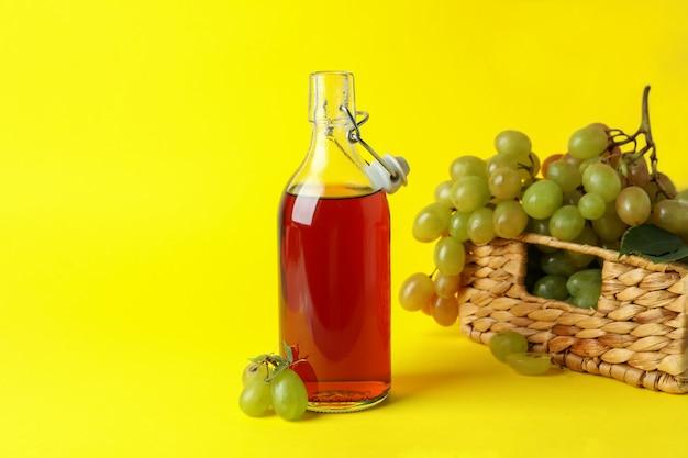 Garrafa de vinagre e cesta com uva em fundo amarelo