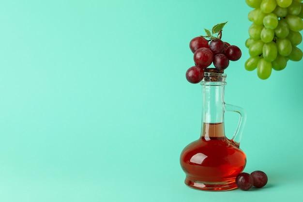 Garrafa de vinagre e uva em fundo de hortelã