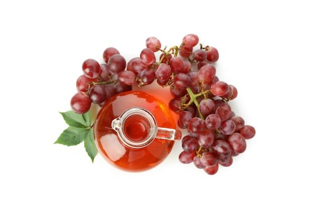 Garrafa de vinagre e uva isolada no fundo branco