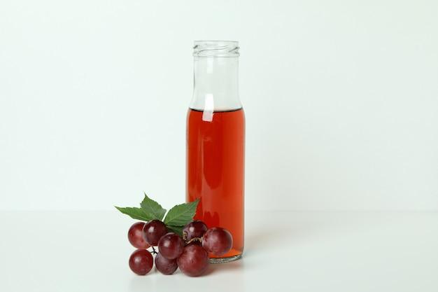 Garrafa de vinagre e uva na mesa branca