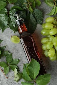 Garrafa de vinagre, uva e folhas na mesa texturizada cinza
