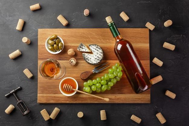 Garrafa de vinho branca, cabeça de queijo, cacho de uvas, mel, nozes e copo de vinho