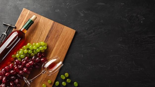 Garrafa de vinho branca, cacho de uvas e um copo de vinho na placa de madeira e fundo preto