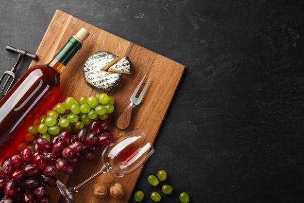Garrafa de vinho branca, cacho de uvas, queijo e copo de vinho na placa de madeira