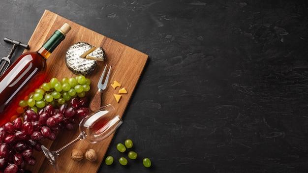 Garrafa de vinho branca, cacho de uvas, queijo e um copo de vinho na madeira