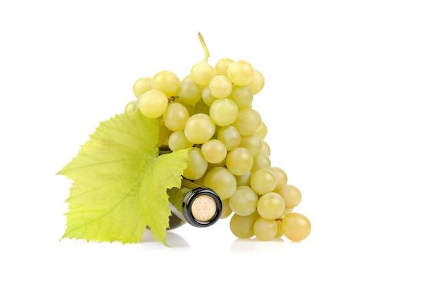 Garrafa de vinho branca e uvas isoladas em branco