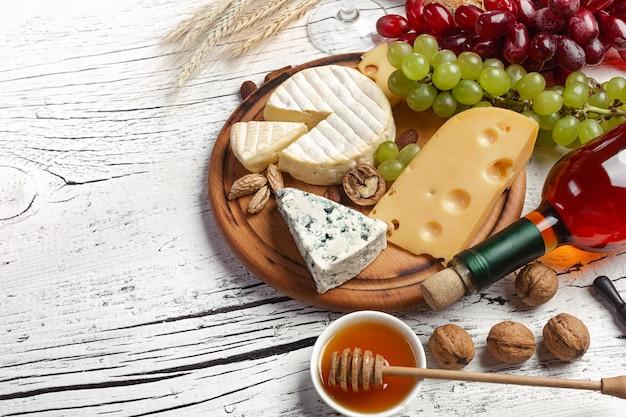Garrafa de vinho branca, uva, mel, nozes e queijo na placa de madeira branca