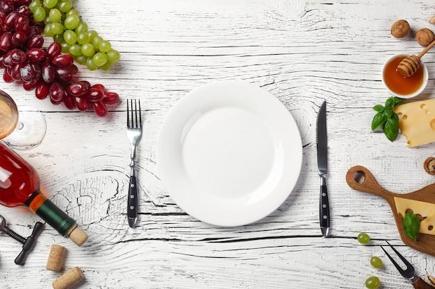 Garrafa de vinho branca, uva, mel, queijo, copo de vinho, prato, faca e garfo na placa de madeira branca
