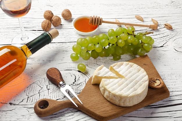 Garrafa de vinho branca, uva, mel, queijo e copo de vinho na placa de madeira branca
