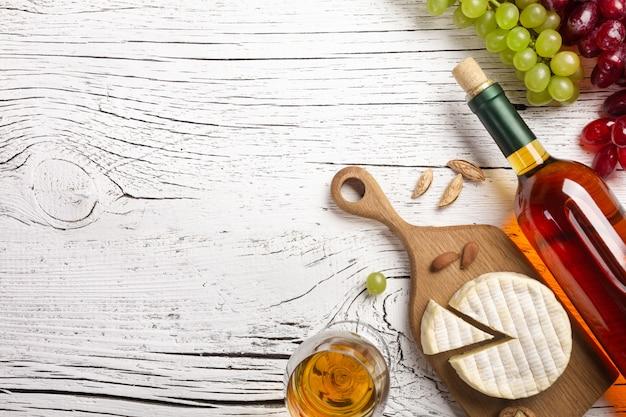 Garrafa de vinho branca, uva, queijo e copo de vinho na placa de madeira branca