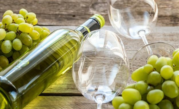 Garrafa de vinho branco com cacho de uva