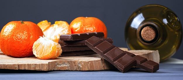 Garrafa de vinho branco com fatias de chocolate ao leite e tangerinas em um carrinho de madeira da floresta. noite romântica para dois close-up.