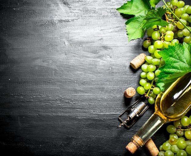 Garrafa de vinho branco com ramos de uvas na mesa de madeira preta.