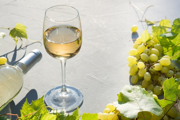 Garrafa de vinho branco com um copo de vinho, uvas maduras na mesa cinza concreta.