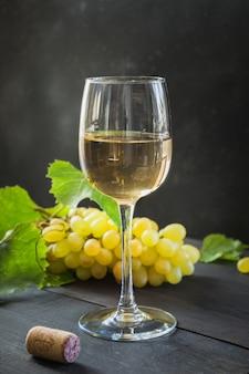 Garrafa de vinho branco com um copo de vinho, uvas maduras na mesa de madeira preta.