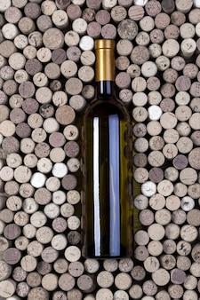 Garrafa de vinho branco e rolhas na mesa de madeira