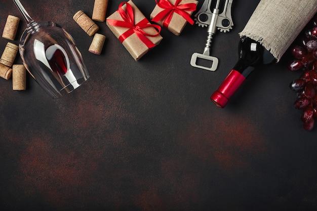 Garrafa de vinho, caixa de presente, uvas vermelhas, saca-rolhas e rolhas, em fundo enferrujado