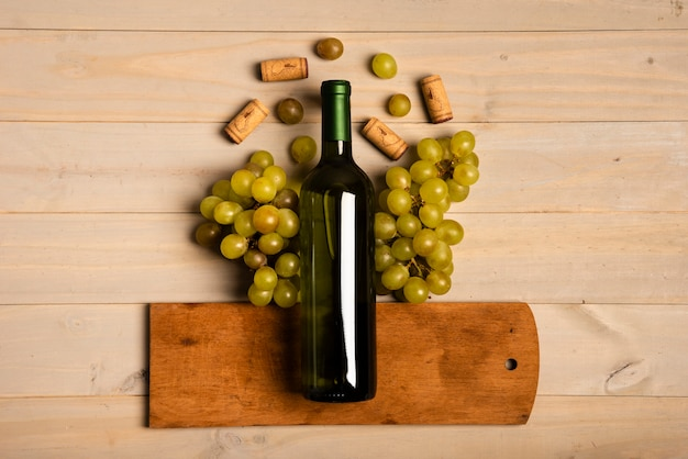 Garrafa de vinho colocado na tábua de cortar perto de uvas