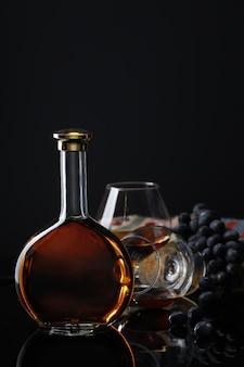 Garrafa de vinho com cálice e uvas