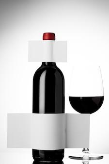 Garrafa de vinho com copo e rótulo em branco