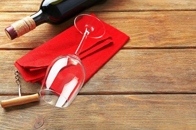 Garrafa de vinho com copo e saca-rolhas no fundo de madeira