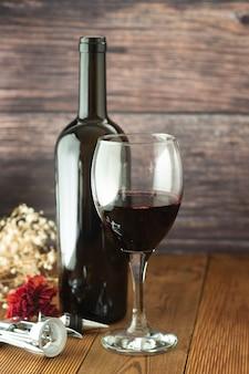 Garrafa de vinho com placa de madeira rústica do corckscrew do copo de vinho, copyspace.