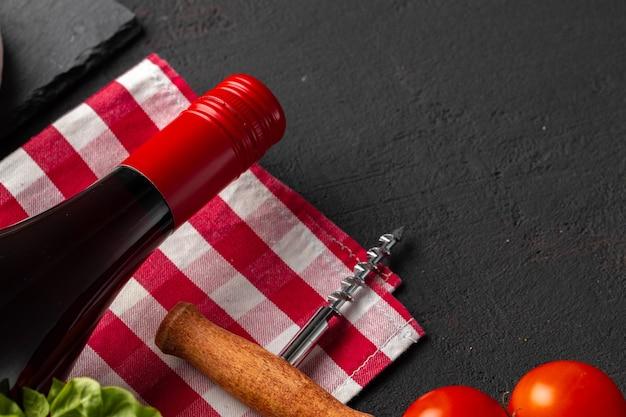 Garrafa de vinho com rolha e tomate cereja em fundo preto