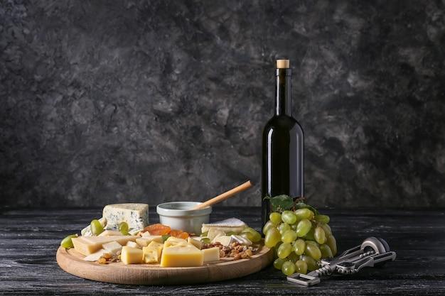 Garrafa de vinho com salgadinhos e uvas maduras na mesa de madeira escura