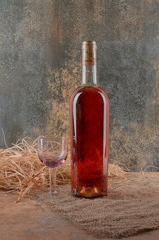 Garrafa de vinho com um copo de vinho na serapilheira.