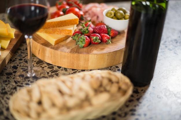 Garrafa de vinho com um copo e um monte de comida