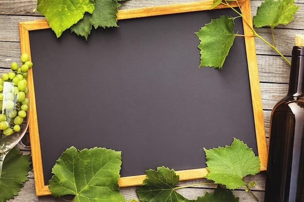 Garrafa de vinho com um copo e uvas em uma mesa de madeira com espaço de cópia