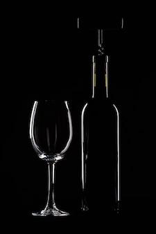 Garrafa de vinho com um copo em fundo preto, saca-rolhas