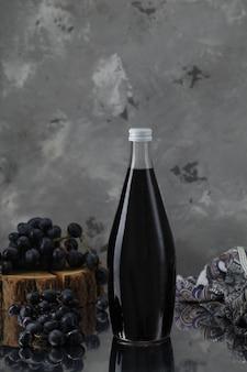 Garrafa de vinho com uvas na peça de madeira