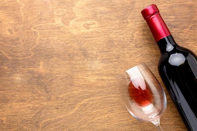 Garrafa de vinho com vista superior e copo com espaço de cópia